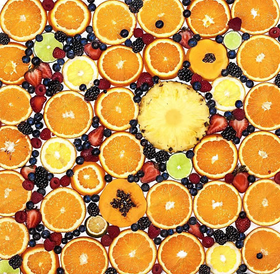 Full-frame top view of colorful fresh fruit slices (oranges pineapple lemon strawberries blueberries raspberries papayas limes) photo