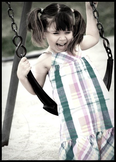 Modelcute little girl having fun day at the park swing set photo