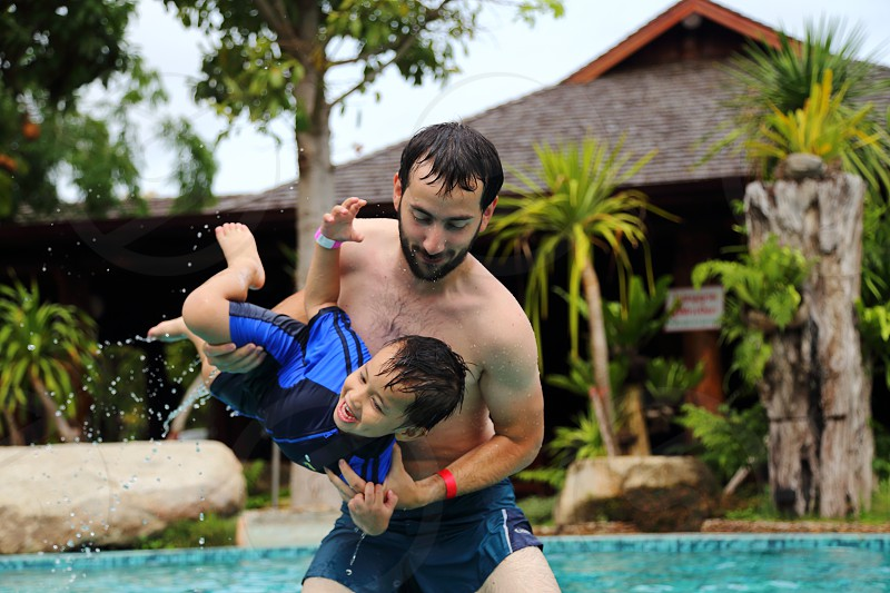 father and son having fun at the swimming pool during summer photo