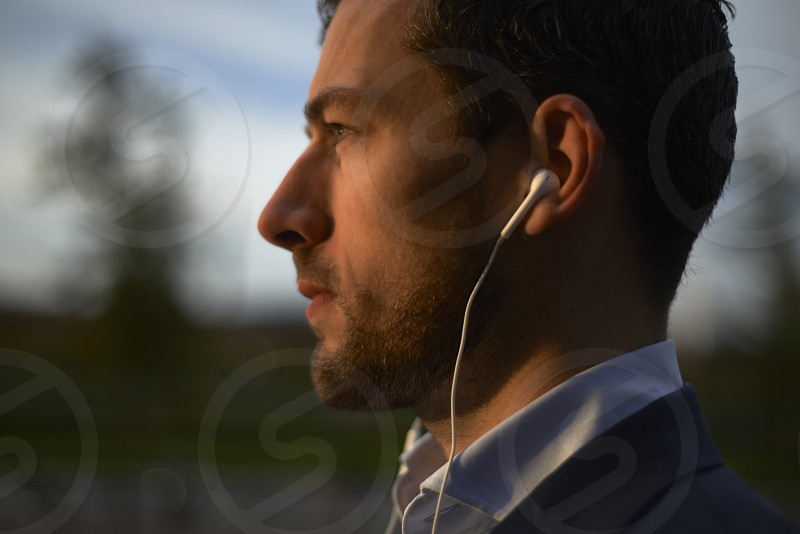 Side profile of a young business man outside in an urban area of the city walking using his mobile phone wearing ear phones photo