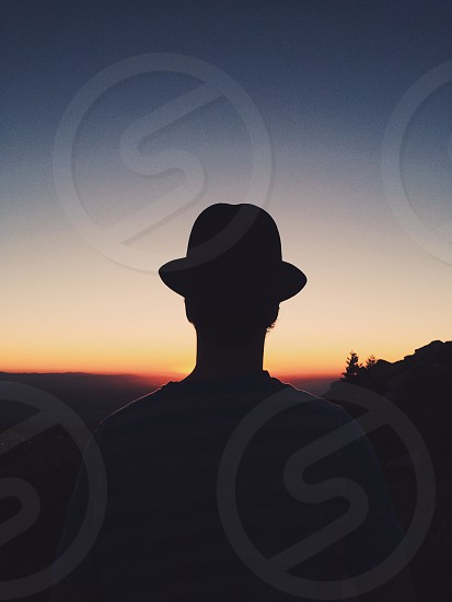 silhouette of person wearing fedora hat during noctilucent photo