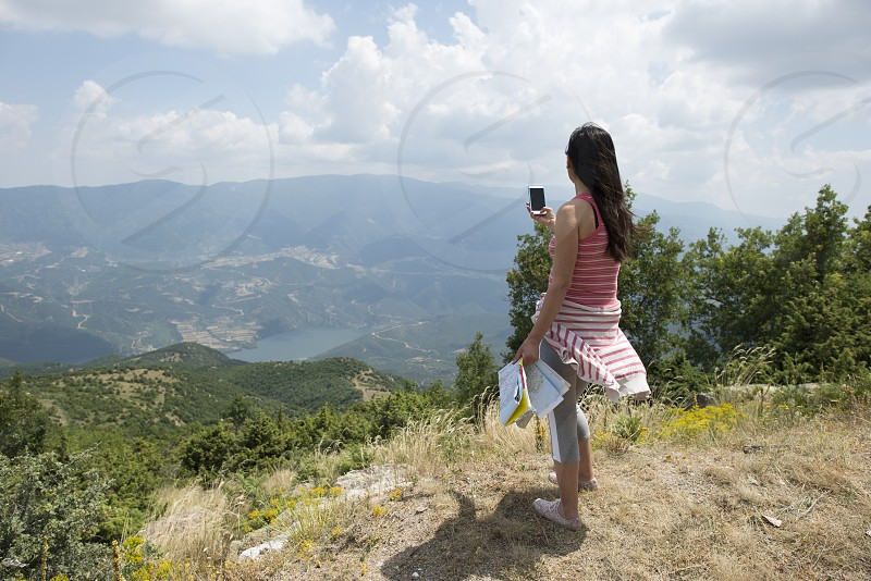 Woman taking pictures with smartphone in the forest photo