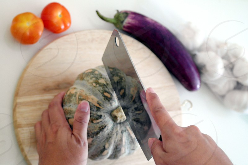 person holding clever knife pointing on green squash on chopping board photo