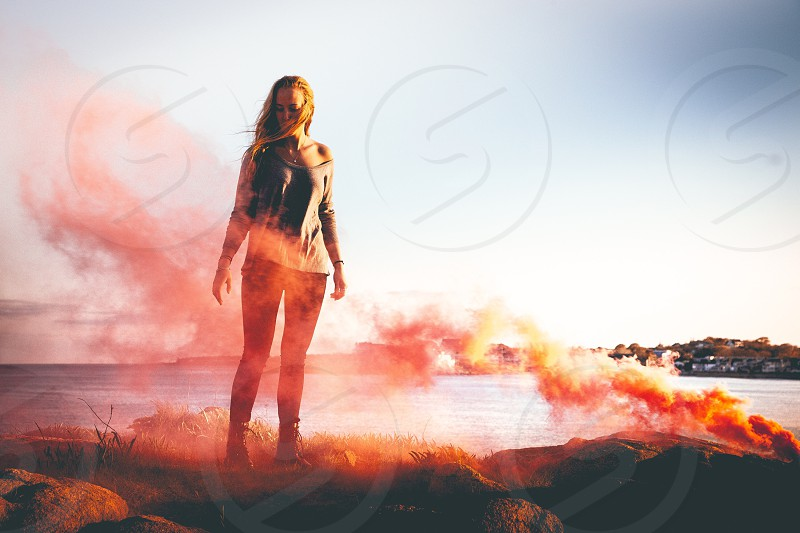 woman standing with red smoke effects photo