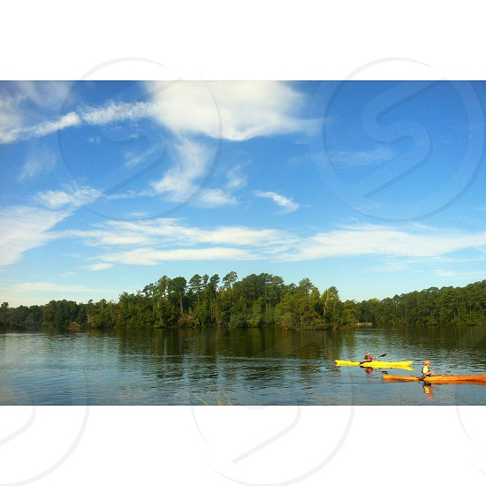 yellow and orange rowing boat in lake with green tree around photograph photo