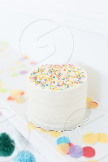 A colorful birthday cake surrounded by confetti photo