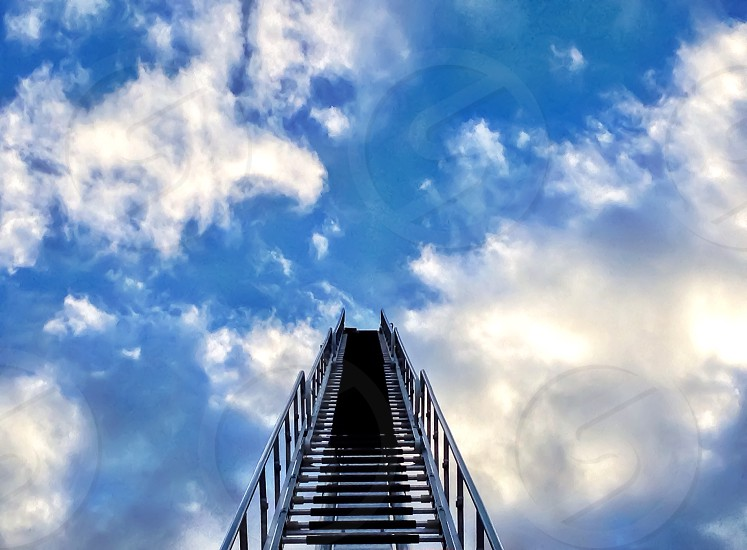 lower angle view of grey staircase under white clouds photo