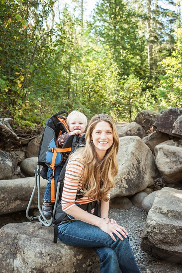 authentic travel woods forest trees hiking backpack child boy riding sitting rock resting trail smile female woman hair portrait happy summer vacation photo