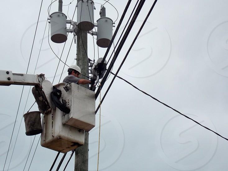 man in cherry picker working on power line photo