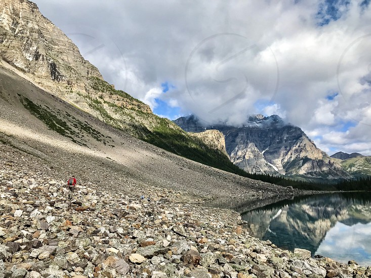 Lone hiker on rocky slope of mountain next to lake  photo