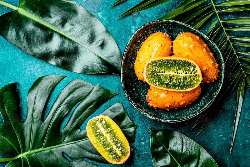 Tropical fruin KIWANO passion fruit in green bowl on turquoise background with tropical palm tree leaves. Top view. Tropical concept. photo