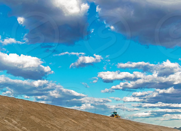 Tractor plowing the land against idyllic blue sky photo