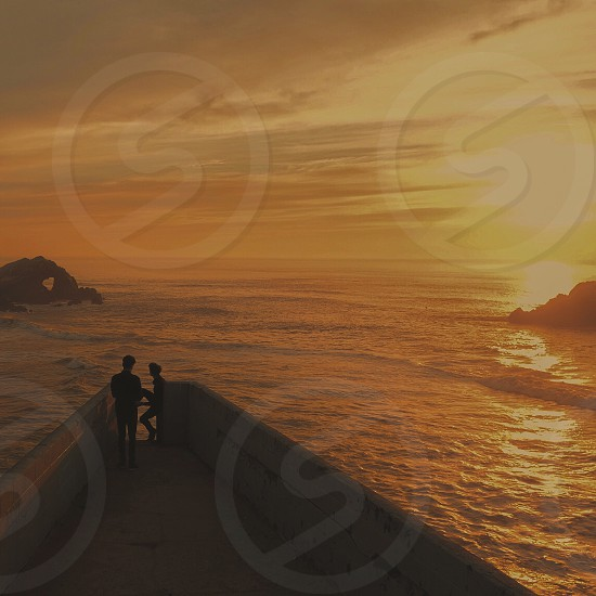 silhouette photography of two person standing on bridge near body of water under orange sky photo