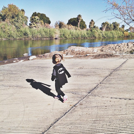 girl in black batman cape walking near river photo