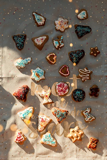 Christmas gingerbread cookies in many shapes decorated with colorful frosting sprinkle icing chocolate coating toppers put on plain fabric photo
