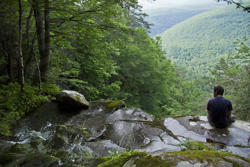 Boy sitting on mountain edge near waterfall in Catskills New York.  Hiking. Camping. Stream. photo
