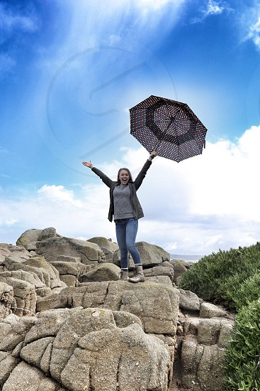 Young Woman with Umbrella on Top of Rocks photo