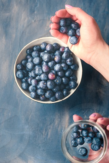 Woman putting freshly gathered blueberries from a jar into a small bowl. Table painted in blue in the background photo
