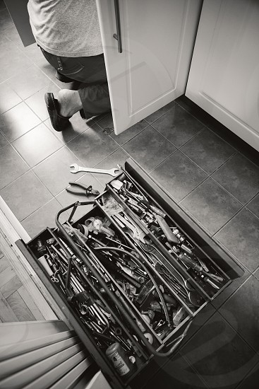 Ordinary lifestyle scene worker and his tools in kitchen servicing something.  photo