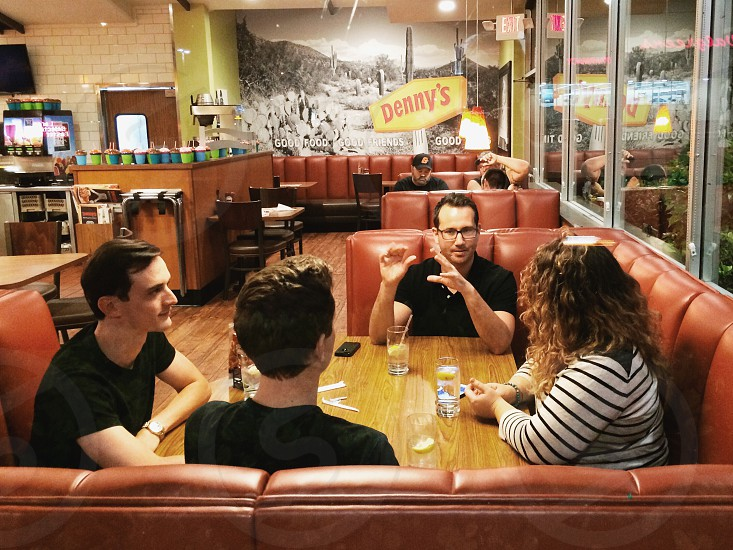 people sitting in front of table and making conversation photo