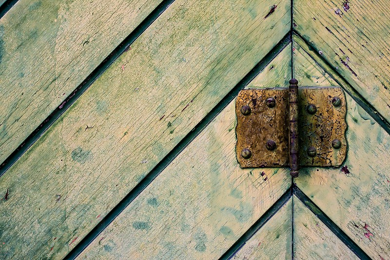 Close-up of old faded green wooden door with rusty hing. photo