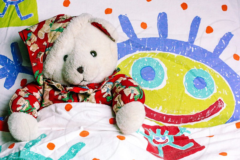 white bear plush toy with red hat on white blue yellow and orange polka dot bed photo