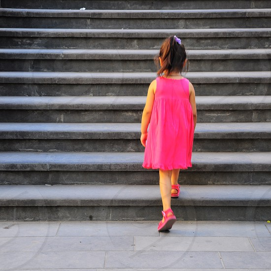 girl wearing a pink dress walking up steps photo