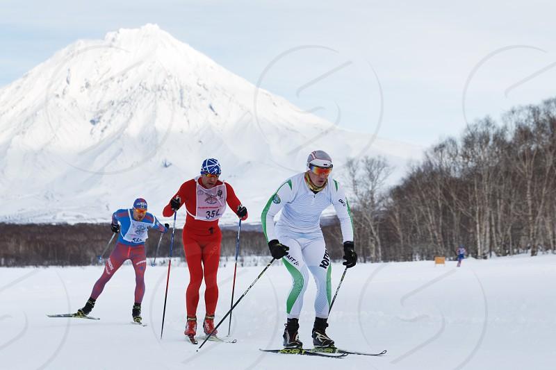 PETROPAVLOVSK CITY KAMCHATKA PENINSULA RUSSIAN FAR EAST - FEB 10 2018: Skiers-men running along the winter ski track on background of Koryak Volcano. All-Russia mass ski race - Ski Track of Russia. photo