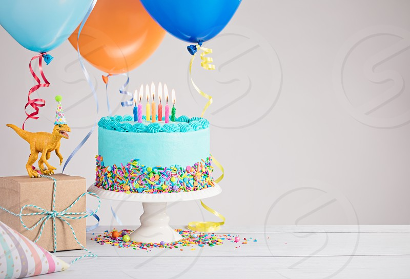 Childs birthday party scene with blue cake gift box toy dinosaur hats and colorful balloons over light grey. photo
