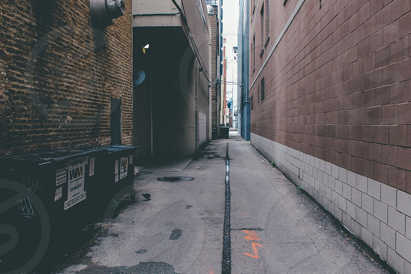 empty gray concrete alley between concrete buildings photo