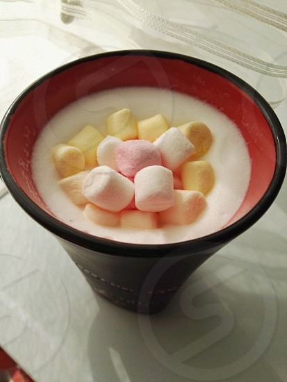 black and red ceramic cup filled of marsh mallow ice cream photo