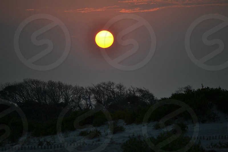 Yellow sun through the dark skies photo