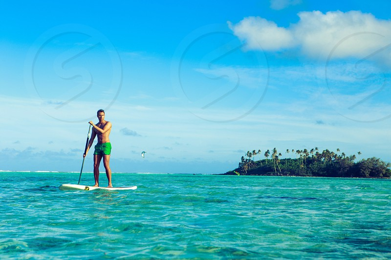 Man on stand up paddleboard on a tropical island photo