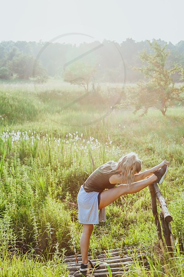 Young woman doing exercise in the nature at sunset photo