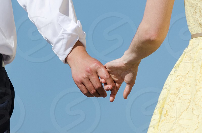 man in white dress shirt holding hands with woman in yellow dress photo