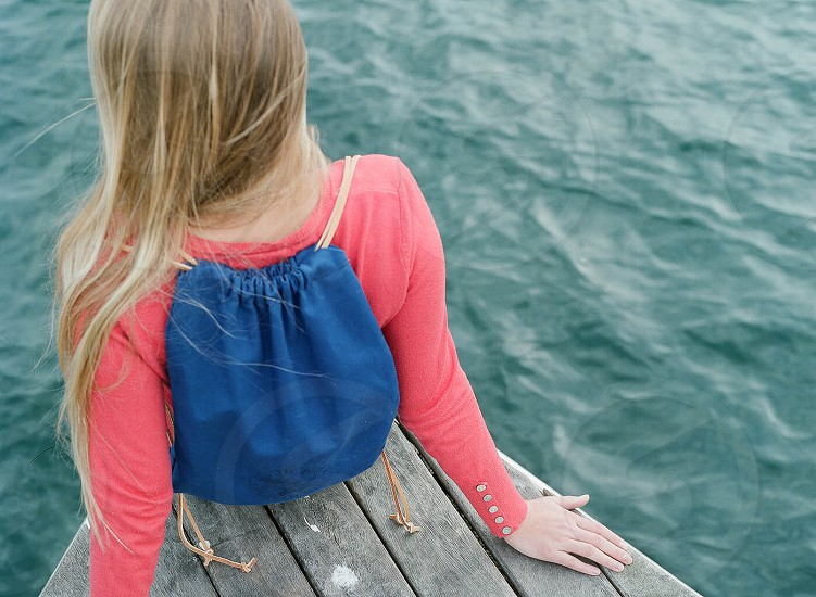 girl in pink shirt with blue back pack sitting on dock photo