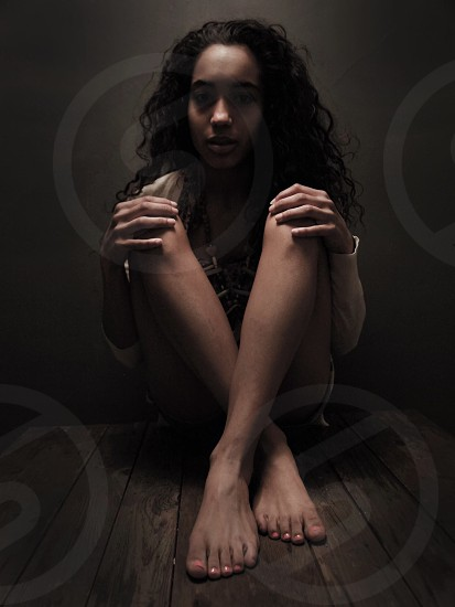 Brown hair woman sitting knees up on a wood table photo