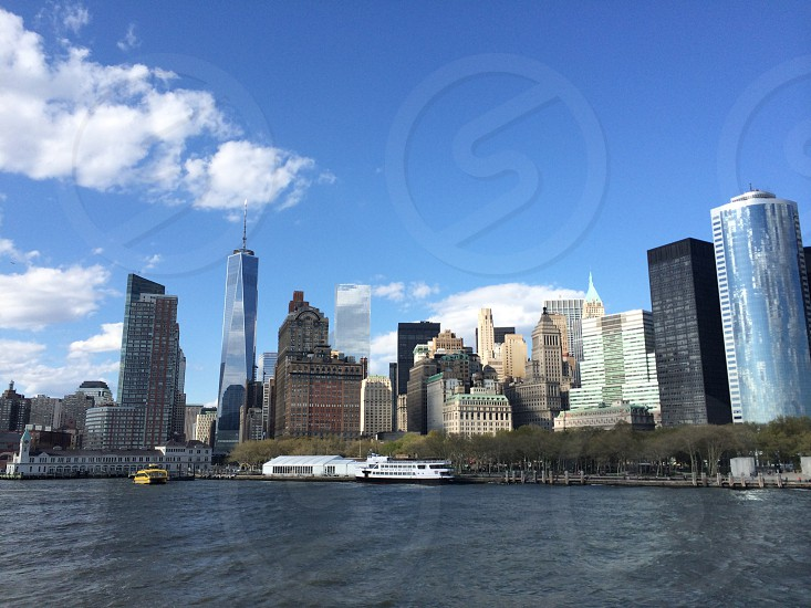 cityscape and body of water under blue sky and white clouds photo