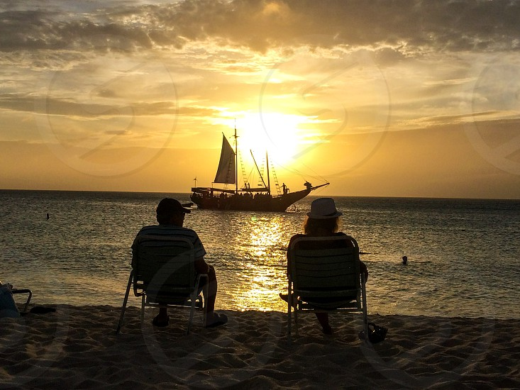 Sunset gold aruba silhouette sailboat beach chairs couple enjoying ocean sea view sky coast  clouds photo