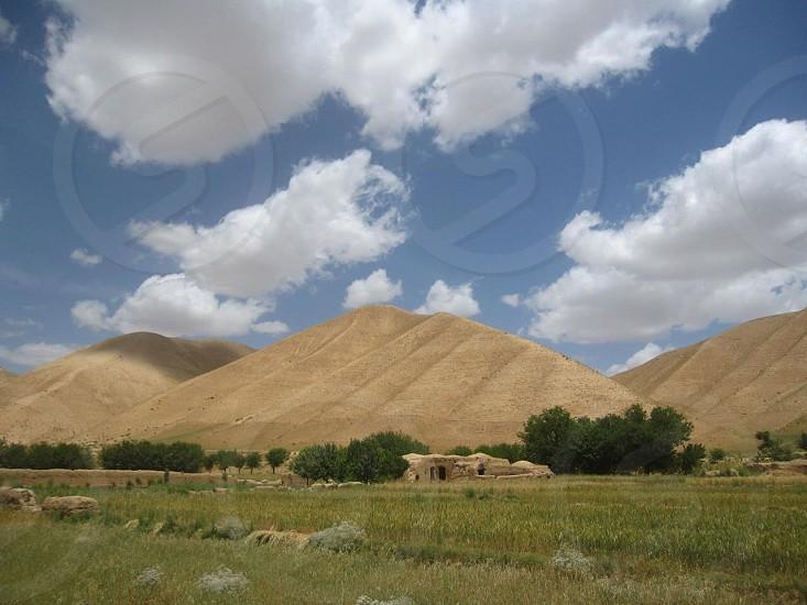 brown hills across green grass field photo