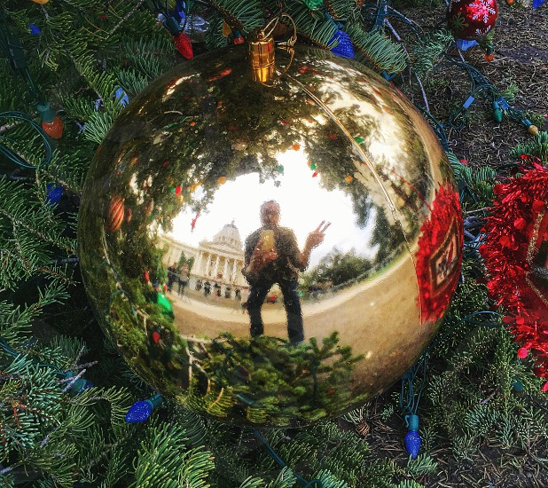 reflection of man making peace hand sign on gold bauble photo