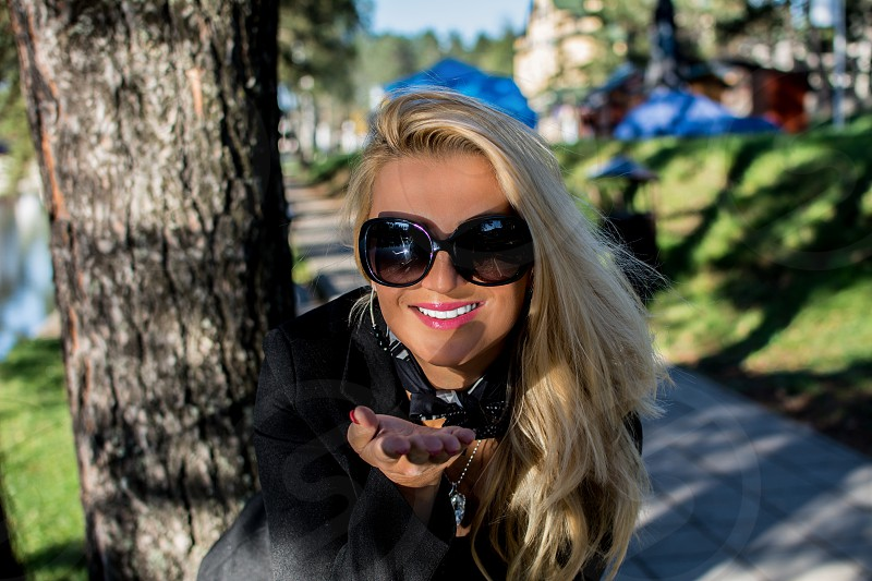 Young beautiful russian girl with blond hair giving a kiss in a park photo