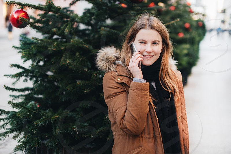 Happy girl talk on her phone and look around with smile impression on her face. Winter time with tree on the street. photo