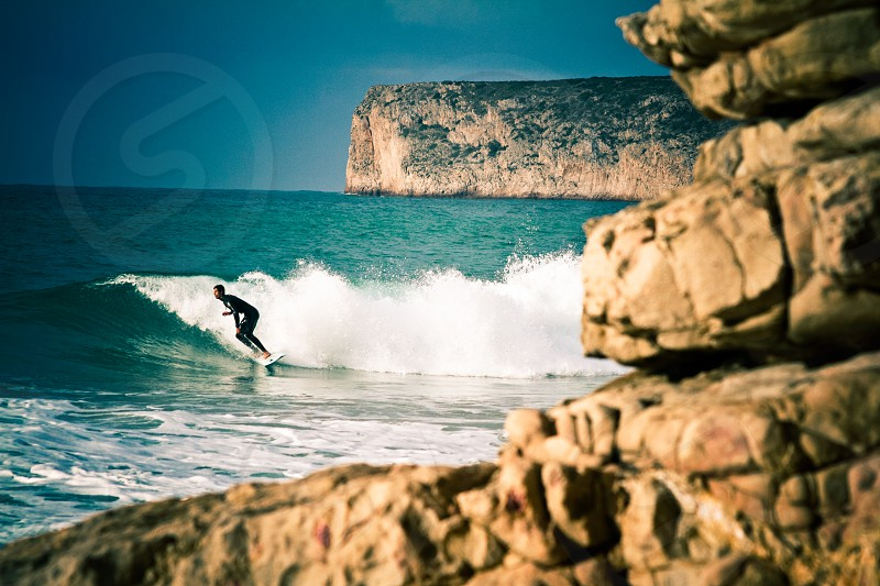 person surfing near ocean wave during daytime photo