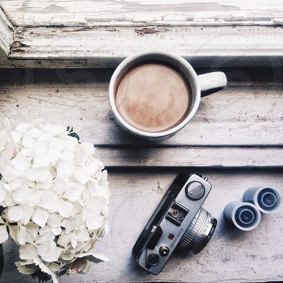 white ceramic coffee cup beside black digital camera on brown wooden table photo