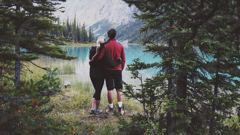 man and woman embracing next to outdoor lake photo