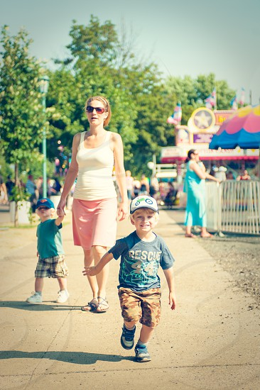 fair carnival festival amusement park park run running boy child happy mother family brothers kids children female sunglasses hat cap pregnant happy summer excited joy excitement blue pink yellow green outside outdoors photo