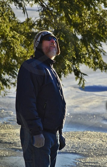portrait winter wonder looking up sunglasses toque hat gloves snow ice lake trees beard jeans blue jacket sunny photo