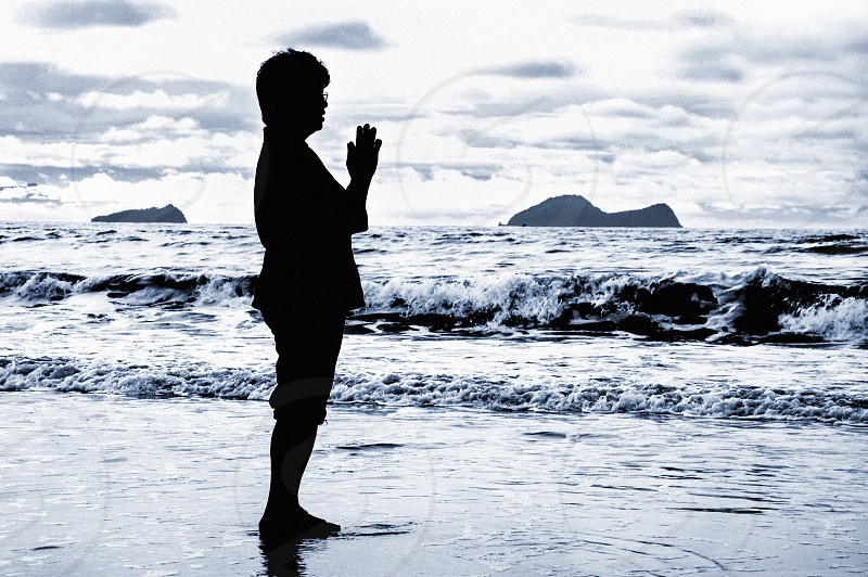 Silhouette of senior adult woman praying on the beach. photo