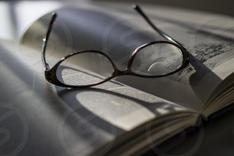 black framed eyeglasses on top of white book photo